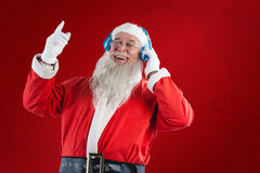 Composite image of santa claus listening to music on headphones. Santa claus listening to music on headphones against red snowflake background Royalty Free Stock Photo