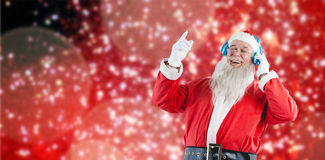 Composite image of santa claus listening to music on headphones. Santa claus listening to music on headphones against white snow and stars on red Royalty Free Stock Image