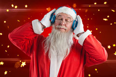 Composite image of santa claus listening to music on headphones with eye closed. Santa Claus listening to music on headphones with eye closed against bright star Stock Photo