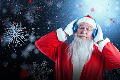 Composite image of santa claus listening to music on headphones with eye closed. Santa Claus listening to music on headphones with eye closed against snowflake Royalty Free Stock Image
