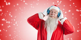 Composite image of santa claus listening to music on headphones with eye closed. Santa Claus listening to music on headphones with eye closed against white light Royalty Free Stock Photos
