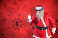 Composite image of santa claus listening to music on mobile phones. Santa Claus listening to music on mobile phones against red snow flake background Royalty Free Stock Photos