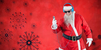 Composite image of santa claus listening to music on mobile phones Stock Images