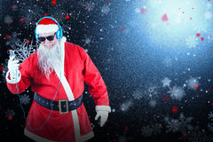 Composite image of santa claus listening to music on mobile phones. Santa Claus listening to music on mobile phones against snowflake pattern Royalty Free Stock Images