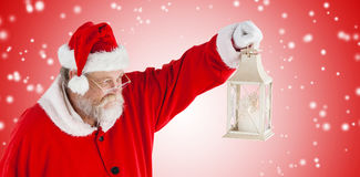 Composite image of santa claus looking at christmas lantern royalty free stock photo