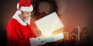 Composite image of santa claus looking at open gift box Stock Image