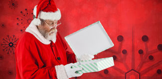 Composite image of santa claus looking at open gift box Royalty Free Stock Image