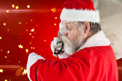 Composite image of santa claus looking at wristwatch Royalty Free Stock Photography