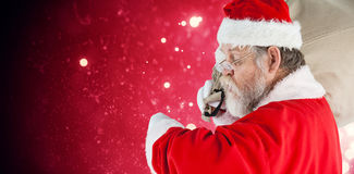 Composite image of santa claus looking at wristwatch Stock Images