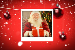 Composite image of santa claus offering a red gift Stock Photos