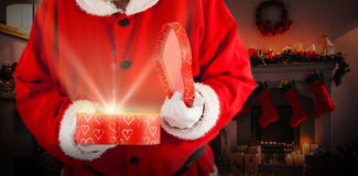 Composite image of santa claus opening a gift box Stock Images