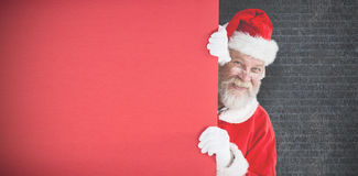 Composite image of santa claus peeking from red board Stock Photos