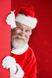 Composite image of santa claus peeking from red board Stock Image
