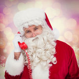 Composite image of santa claus on the phone. Santa claus on the phone against glowing christmas background royalty free stock photography