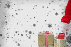 Composite image of santa claus picking christmas gift Royalty Free Stock Image