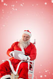 Composite image of santa claus playing game on digital pc Royalty Free Stock Photo