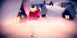 Composite image of santa claus points at something Stock Photography