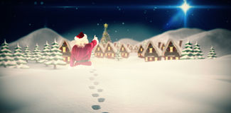 Composite image of santa claus points at something Stock Images