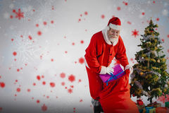 Composite image of santa claus putting presents in bag by christmas tree Stock Image