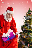 Composite image of santa claus putting presents in bag by christmas tree Royalty Free Stock Photos