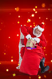 Composite image of santa claus putting presents in christmas bag Royalty Free Stock Photography