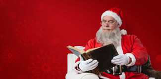 Composite image of santa claus reading bible Royalty Free Stock Photography