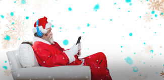Composite image of santa claus reading on digital tablet Stock Images