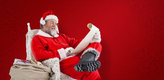 Composite image of santa claus reading wish list on scroll against white background Royalty Free Stock Images
