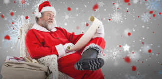Composite image of santa claus reading wish list on scroll against white background Stock Photos