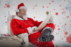 Composite image of santa claus reading wish list on scroll against white background Royalty Free Stock Photography