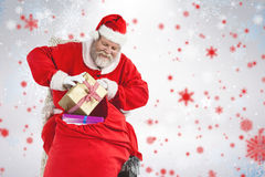 Composite image of santa claus removing presents from christmas bag Stock Image