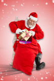 Composite image of santa claus removing presents from christmas bag Royalty Free Stock Photo