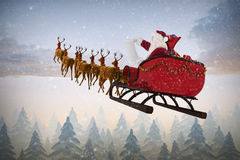 Composite image of santa claus riding on sled during christmas. Santa Claus riding on sled during Christmas against snow falling on fir tree forest Stock Photography
