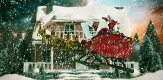 Composite image of santa claus riding on sled during christmas. Santa Claus riding on sled during Christmas against snowy landscape with fir trees Royalty Free Stock Photography