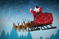 Composite image of santa claus riding on sleigh during christmas. Santa Claus riding on sleigh during Christmas against fir tree forest Royalty Free Stock Images