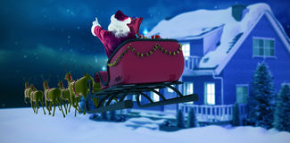 Composite image of santa claus riding on sleigh during christmas. Santa Claus riding on sleigh during Christmas against starry sky over fir trees Stock Photos