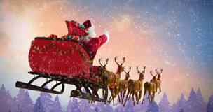 Composite image of santa claus riding on sleigh with gift box. Santa Claus riding on sleigh with gift box against fir tree forest Royalty Free Stock Photography