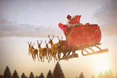 Composite image of santa claus riding on sleigh with gift box. Santa Claus riding on sleigh with gift box against snow falling on fir tree forest Stock Photos