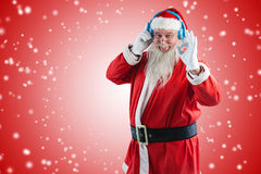 Composite image of santa claus showing hand okay sign while listening to music on headphones Royalty Free Stock Image