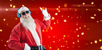 Composite image of santa claus showing hand sign while listening to music on headphones Stock Images