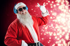 Composite image of santa claus showing hand sign while listening to music on headphones Royalty Free Stock Photo