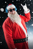 Composite image of santa claus showing hand yo sign while listening to music on headphones Royalty Free Stock Photography