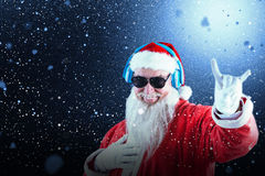 Composite image of santa claus showing horn sign while listening to music on headphones Stock Photography