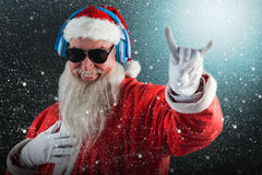 Composite image of santa claus showing horn sign while listening to music on headphones Royalty Free Stock Photos