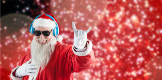 Composite image of santa claus showing horn sign while listening to music on headphones Stock Images