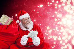 Composite image of santa claus sitting by sack full of gifts counting currency notes Stock Images
