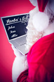 Composite image of santa claus using his laptop Royalty Free Stock Photography