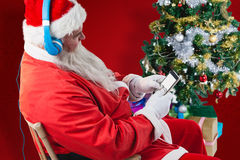 Composite image of santa claus using mobile phone with christmas tree Royalty Free Stock Photos