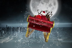 Composite image of santa flying his sleigh. Santa flying his sleigh against balcony overlooking city Stock Photos