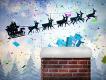 Composite image of santa flying his sleigh behind chimney Stock Photo